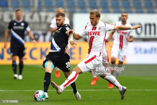 Marcel Hartel of DSC Arminia Bielefeld is challenged by Sebastian Andersson of 1 FC Koln during the Bundesliga match between DSC Arminia Bielefeld...