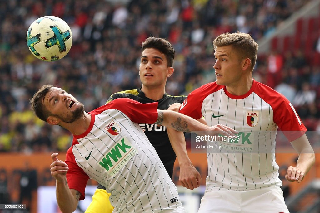Marcel Heller of Augsburg, Christian Pulisic of Dortmund and Alfred Finnbogason of Augsburg during the Bundesliga match between FC Augsburg and Borussia Dortmund at WWK-Arena on September 30, 2017 in Augsburg, Germany.