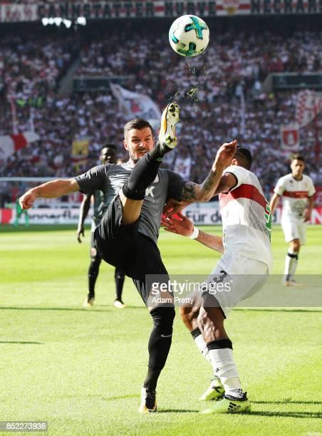 Marcel Heller of Augsburg is challenged by Dennis Aogo of VfB Stuttgart during the Bundesliga match between VfB Stuttgart and FC Augsburg at...