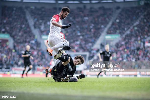 AUGSBURG GERMANY FEBRUARY Image has been digitally enhanced Marcel Heller of Augsburg is tackled by Benjamin Pavard of Stuttgart during the...