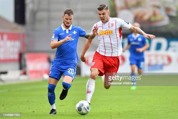 Marcel Heller of Darmstadt is challenged by Erik Wekesser of Regensburg during the Second Bundesliga match between SSV Jahn Regensburg and SV...