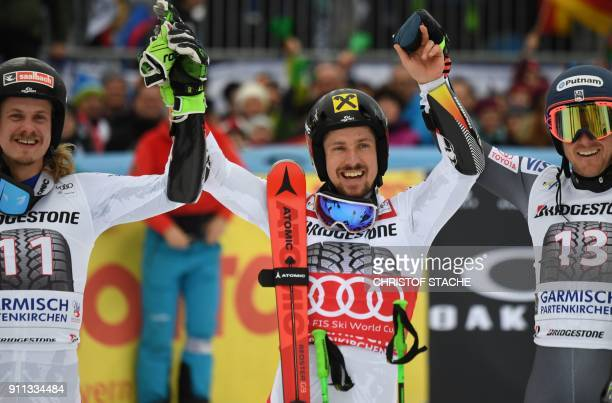 Marcel Hirscher celebrates victory with runner up compatriot Manuel Feller and third placed Ted Ligety of the USA during the men's Giant Slalom at...