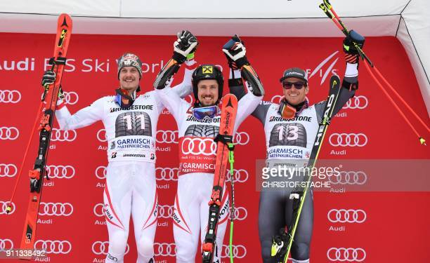 Marcel Hirscher celebrates victory with runner up compatriot Manuel Feller and third placed Ted Ligety of the USA on the podium after the men's Giant...