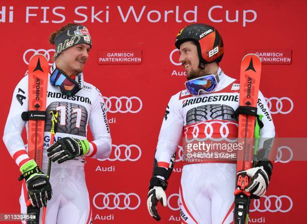 Marcel Hirscher celebrates victory with runner up compatriot Manuel Feller on the podium after the men's Giant Slalom at the FIS Alpine Skiing World...