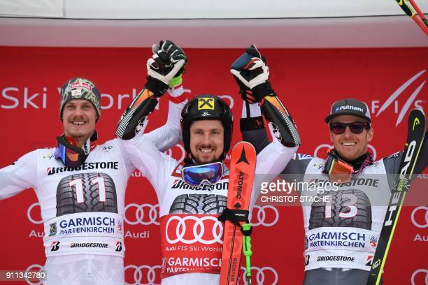 Marcel Hirscher of Austria celebrates victory with runner up compatriot Manuel Feller and third placed Ted Ligety of the USA on the podium after the...