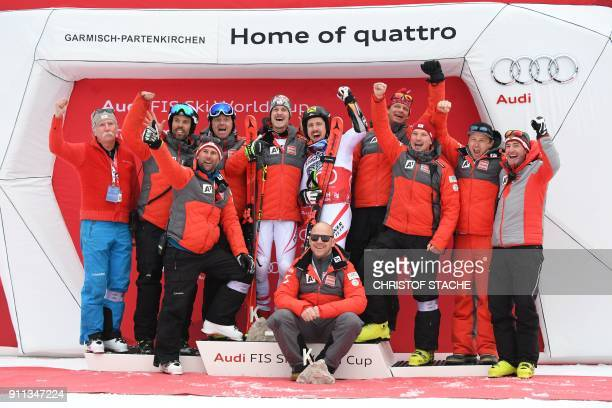 Marcel Hirscher of Austria celebrates victory with runner up compatriot Manuel Feller and team members on the podium after the men's Giant Slalom at...