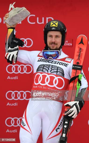 Marcel Hirscher of Austria holds trophy aloft on the podium after winning the men's Giant Slalom at the FIS Alpine Skiing World Cup in...