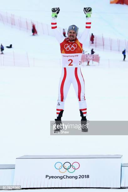 Marcel Hirscher of Austria jumps onto the podium as he celebrates winning gold following the Men's Alpine Combined Slalom on day four of the...