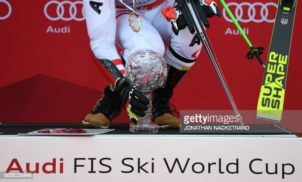Marcel Hirscher of Austria winner of the men's Giant Slalom overall World Cup holds his trophy on the podium after the Men's Giant Slalom event of...