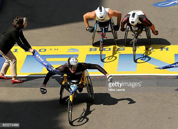 Marcel Hug of Switzerland celebrates as he crosses the finish line to win the men's push rim wheelchair race ahead of Kurt Fearnley of Australia and...