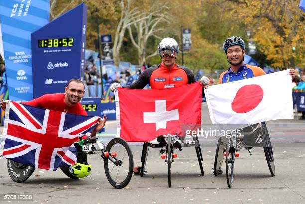 Marcel Hug of Switzerland celebrates winning the Professional Men's Wheelchair Division with John Charles Smith of the United Kingdom and Sho...