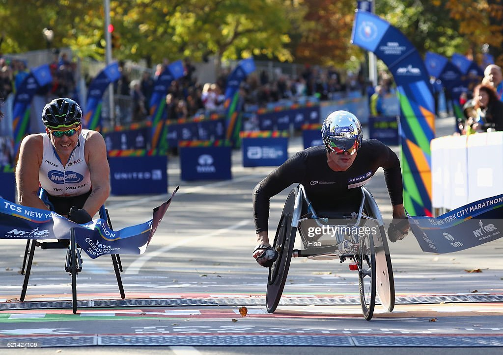 Marcel Hug (R) of Switzerland crosses the finish line to finish first alongside second place Kurt Fearnley (L) of Australia in the Pro Wheelchair Men's event during the 2016 TCS New York City Marathon in Central Park on November 6, 2016 in New York City.