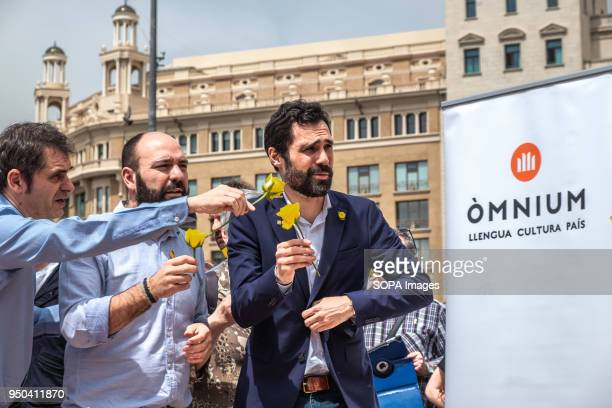 Marcel Mauri vicepresident of Òmnium Cultural and Roger Torrent president of the Catalan Parliament table are seen in the mural of yellow roses that...