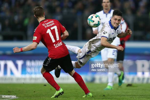 Marcel Mehlem of Karlsruhe is challenged by Sebastian Schiek of Grossaspach during the 3 Liga match between Karlsruher SC and SG Sonnenhof...
