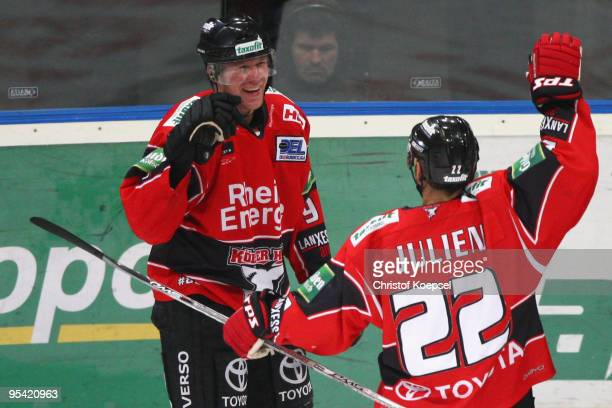Marcel Mueller of the Haie celebrates the forth goal with Stéphane Julien during the DEL match between Koelner Haie and Frankfurt Lions at the...