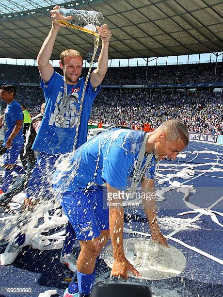 Marcel Ndjeng of Berlin gets a beer shower after winning the championship after the Second Bundesliga match between Hertha BSC Berlin and FC Energie...