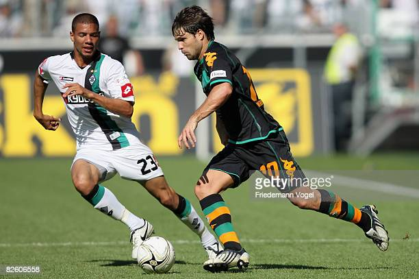Marcel Ndjeng of Gladbach challenges Diego of Werder for the ball during the Bundesliga match between Borussia Moenchengladbach and Werder Bremen at...