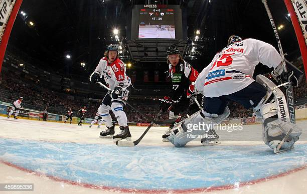 Marcel Ohmann of Koelner Haie and jonas Mueller of Eisbaeren Berlin battle for the puck in front of the net during the DEL Ice Hockey match between...