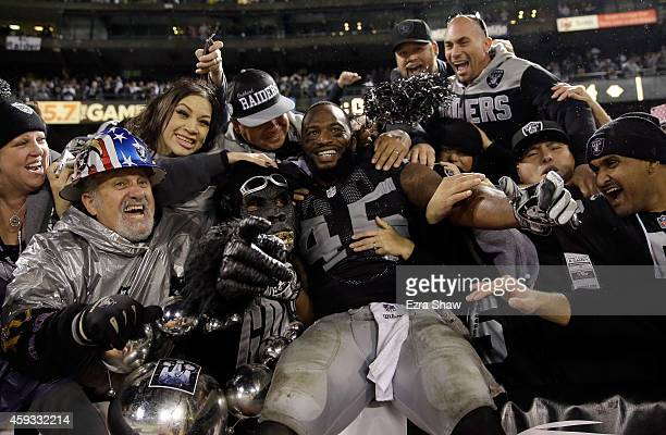 Marcel Reece of the Oakland Raiders celebrates with fans in the Black Hole after the Raiders beat the Kansas City Chiefs at Oco Coliseum on November...