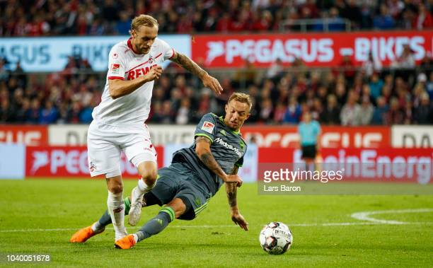 Marcel Risse of Koeln is tackeled by Sonny Kittel of Ingolstadt in the penalty box during the Second Bundesliga match between 1 FC Koeln and FC...