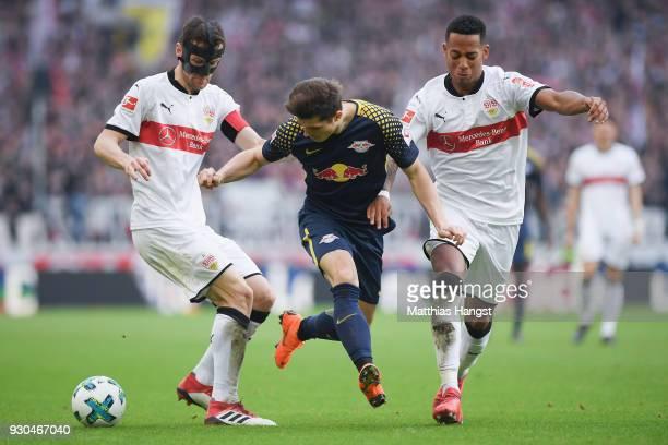 Marcel Sabitzer of Leipzig is challenged by Christian Gentner and Dennis Aogo of Stuttgart during the Bundesliga match between VfB Stuttgart and RB...
