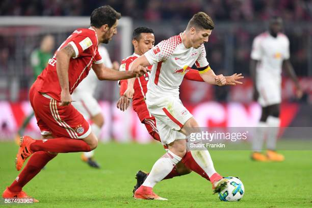 Marcel Sabitzer of Leipzig is challenged by Thiago Alcantara of Bayern Muenchen and Javi Martinez of Bayern Muenchen during the Bundesliga match...