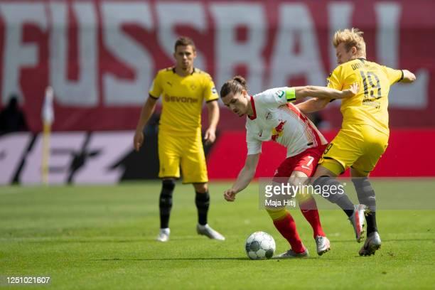 Marcel Sabitzer of RB Leipzig and Julian Brandt of Borussia Dortmund battle for possession during the Bundesliga match between RB Leipzig and...