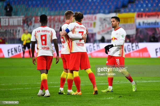 Marcel Sabitzer of RB Leipzig celebrates with teammates Dani Olmo and Justin Kluivert after scoring his team's first goal during the Bundesliga match...