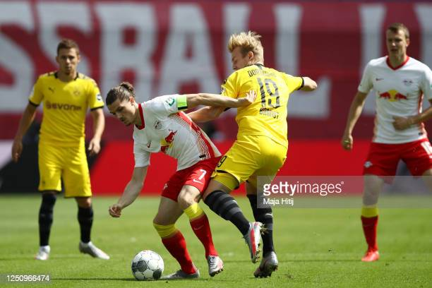 Marcel Sabitzer of RB Leipzig is challenged by Julian Brandt of Borussia Dortmund during the Bundesliga match between RB Leipzig and Borussia...