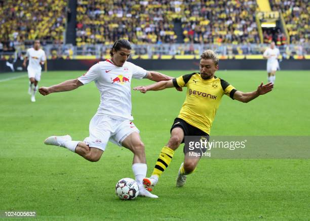 Marcel Sabitzer of RB Leipzig is challenged by Marcel Schmelzer of Borussia Dortmund during the Bundesliga match between Borussia Dortmund and RB...