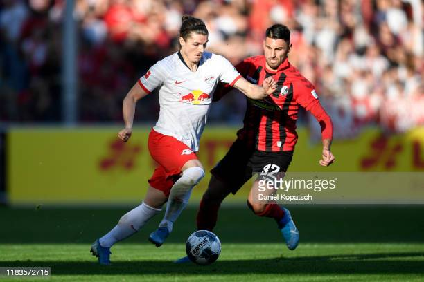 Marcel Sabitzer of RB Leipzig is challenged by Vincenzo Grifo of Sport-Club Freiburg during the Bundesliga match between Sport-Club Freiburg and RB...