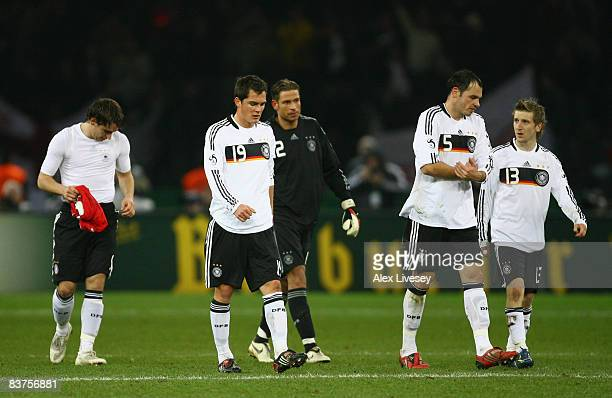 Marcel Schafer, Heiko Westermann and Marko Marin of Germany show their dejection following their team's defeat at the end of the International...
