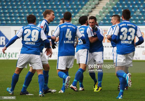Marcel Schied of Rostock celebrates with his team mates after scoring his team's first goal during the Second Bundesliga match between FC Hansa...
