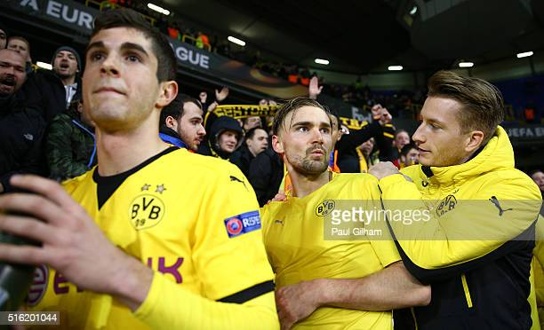 Marcel Schmelzer and Marco Reus of Borussia Dortmund celebrate victory with their fans after the UEFA Europa League round of 16 second leg match...