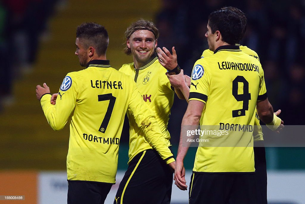 Marcel Schmelzer (C) celebrates his team's second goal with team mates Moritz Leitner (L) and Robert Lewandowski during the second round match of the DFB Cup between VfR Aalen and Borussia Dortmund at Scholz-Arena on October 30, 2012 in Aalen, Germany.