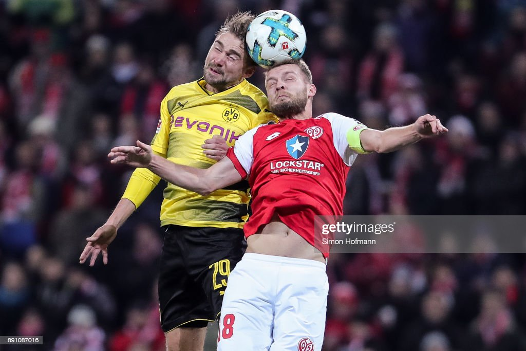Marcel Schmelzer #29 of Borussia Dortmund (L) and Daniel Brosinski #18 of FSV Mainz 05 battle for the ball during the Bundesliga match between 1. FSV Mainz 05 and Borussia Dortmund at Opel Arena on December 12, 2017 in Mainz, Germany.