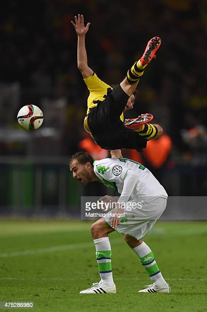 Marcel Schmelzer of Borussia Dortmund is tackled by Bas Dost of VfL Wolfsburg during the DFB Cup Final match between Borussia Dortmund and VfL...
