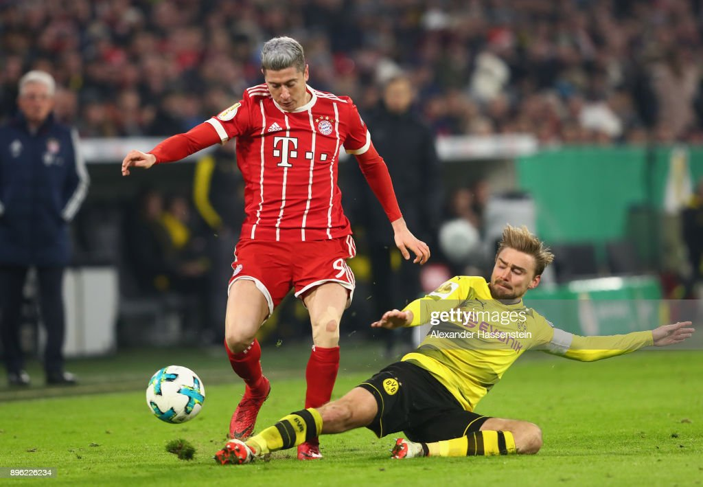 Marcel Schmelzer of Borussia Dortmund tackles Robert Lewandowski of Bayern Muenchen during the DFB Cup match between Bayern Muenchen and Borussia Dortmund at Allianz Arena on December 20, 2017 in Munich, Germany.