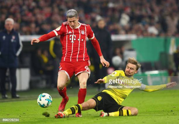 Marcel Schmelzer of Borussia Dortmund tackles Robert Lewandowski of Bayern Muenchen during the DFB Cup match between Bayern Muenchen and Borussia...