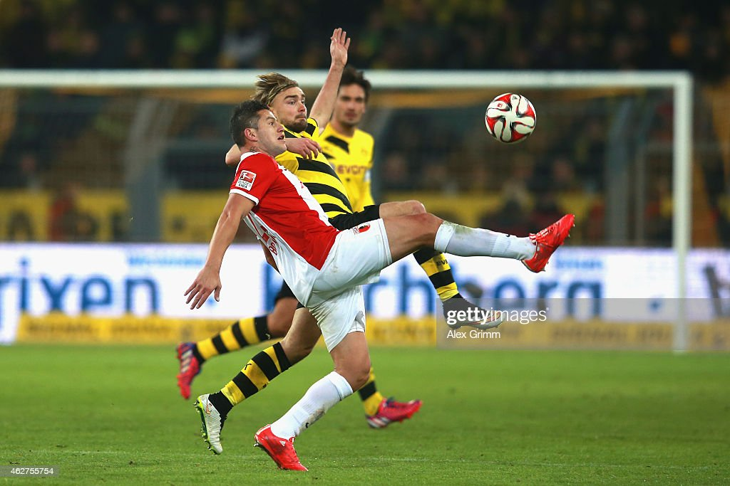 Marcel Schmelzer of Dortmund battles for the ball with Raul Bobadilla (L) of Augsburg during the Bundesliga match between Borussia Dortmund and FC Augsburg at Signal Iduna Park on February 4, 2015 in Dortmund, Germany.