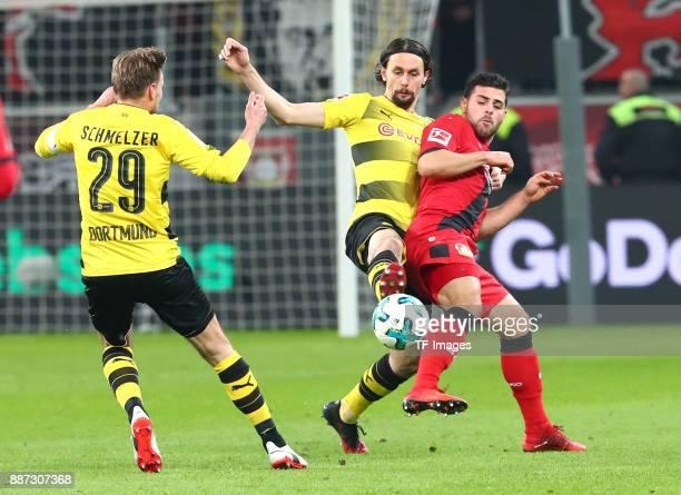 Marcel Schmelzer of Dortmund Neven Subotic of Dortmund and Kevin Volland of Leverkusen battle for the ball during the Bundesliga match between Bayer...