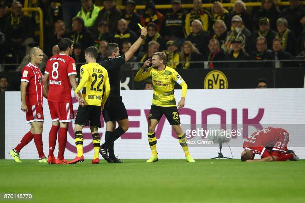 Marcel Schmelzer of Dortmund receives a yellow card from referee Tobias Stieler following a foul on Joshua Kimmich of Bayern Muenchen during the...