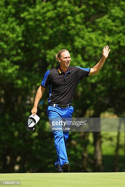 Marcel Siem of Germany celebrates his hole in one on the second hole during the final round of the BMW PGA Championship on the West Course at...