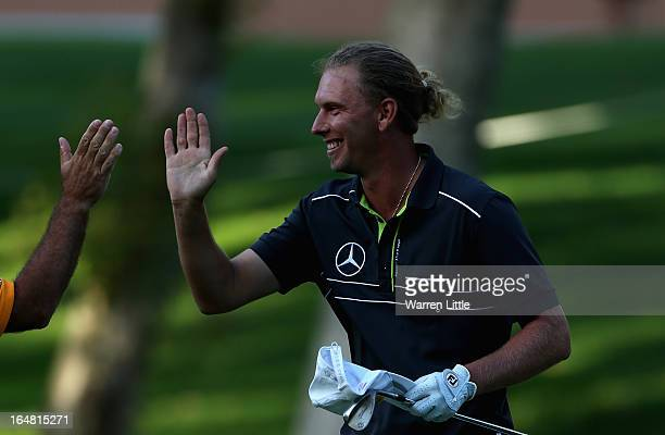 Marcel Siem of Germany is congratulated after holing his bunker shot for a birdie on the 18th green during the first round of the Trophee du Hassan...