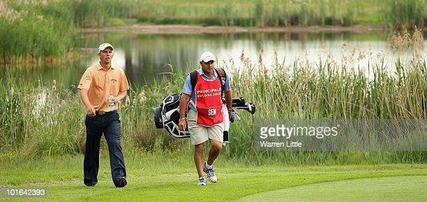 Marcel Siem of Germany walks with his caddie Kyle Roadley up the 14th fairway during the third round of the Celtic Manor Wales Open on The Twenty Ten...