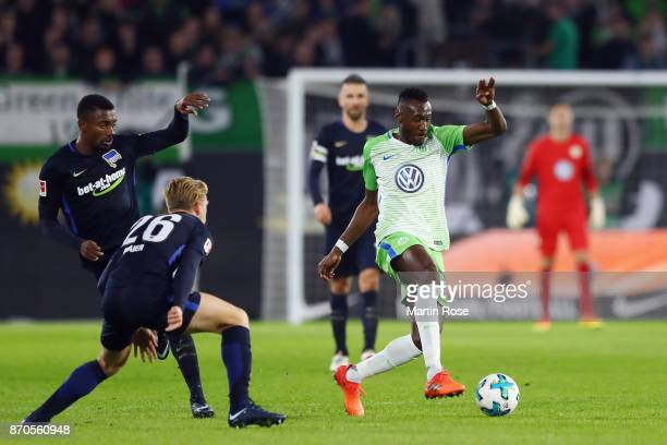 Marcel Tisserand of Wolfsburg is challenged by Arne Maier and Salomon Kalou of Berlin during the Bundesliga match between VfL Wolfsburg and Hertha...