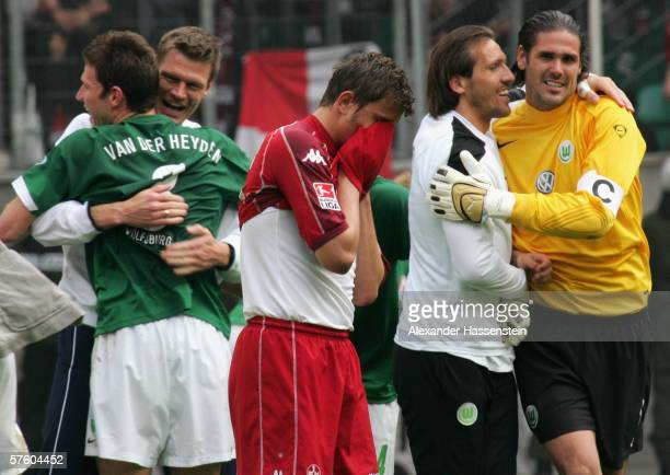 Marcel Ziemer of Kaiserslautern looks dejected after being relegated with his team whilst players of Wolfsburg celebrating winning the match and...