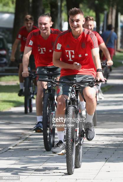 Marcel Zylla and Ryan Johansson of FC Bayern Muenchen ride bicycles during a training session near the club's Saebener Strasse training ground on...