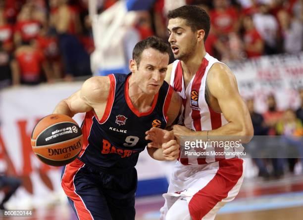 Marcelinho Huertas #9 of Baskonia Vitoria Gasteiz competes with Vassilis Toliopoulos #4 of Olympiacos Piraeus during the 2017/2018 Turkish Airlines...
