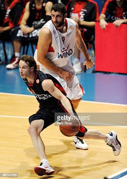 Marcelinho Huertas #9 of Caja Laboral takes the ball past Ioannis Bourousis #9 of Olympiacos Piraeus during the Euroleague Basketball 20092010 Last...
